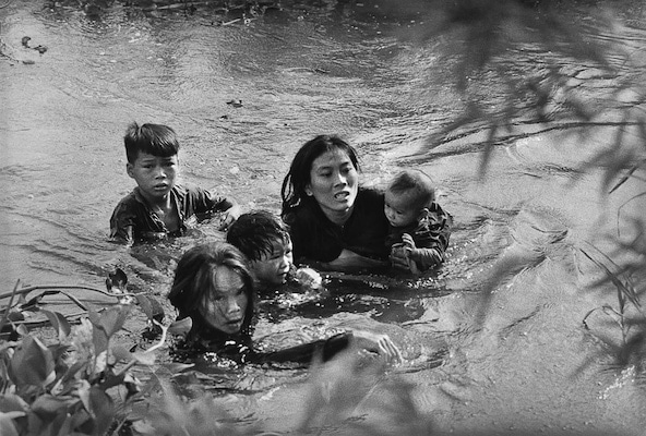 Kyōichi Sawada (Japan), A mother and her children wade across a river in Vietnam to escape U.S. bombing, 1965.