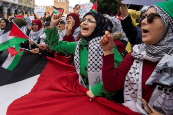 Pro-Palestinian protesters wave Palestinian flags and chant slogans against the US and Israel in Rabat on 10 December, 2017 (AFP)