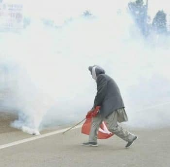 Dharampal Seel, a senior Kisan Sabha leader from Punjab, uses his Red Flag to push a tear gas canister, 27 November 2020.