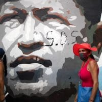 Government supporters walk past a mural depicting the late president Hugo Chavez during a closing campaign rally for the upcoming parliamentary elections, in Caracas, Venezuela, Thursday, Dec. 3, 2020. The South American nation is caught in a deepening political and economic crisis, despite holding the world's largest oil reserves. (AP Photo/Ariana Cubillos)