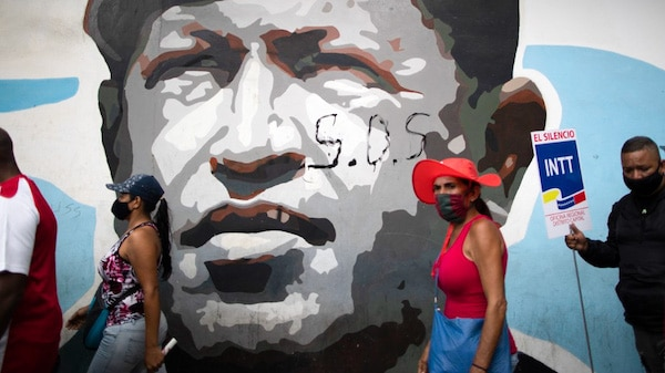 | Government supporters walk past a mural depicting the late president Hugo Chavez during a closing campaign rally for the upcoming parliamentary elections in Caracas Venezuela Thursday Dec 3 2020 The South American nation is caught in a deepening political and economic crisis despite holding the worlds largest oil reserves AP PhotoAriana Cubillos | MR Online