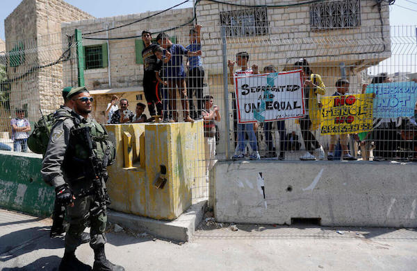 ISRAELI BORDER POLICEMEN STAND GUARD DURING A DEMONSTRATION ORGANIZED BY YOUNG PALESTINIANS IN HEBRON ON SEPTEMBER 3, 2017, AGAINST A RECENT DECISION BY ISRAEL GIVING JEWISH SETTLEMENT ENCLAVES IN HEBRON THE AUTHORITY TO MANAGE THEIR OWN MUNICIPAL AFFAIRS. (PHOTO: WISAM HASHLAMOUN/APA IMAGES)