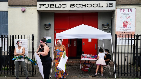 Teachers prepare an outdoor learning demonstration for students to display methods schools can use to continue on-site education during the coronavirus pandemic, Sept. 2, 2020, at P.S. 15 in the Red Hook neighborhood of the Brooklyn borough of New York. John Minchillo | AP