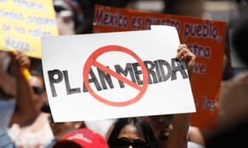 """A supporter of the peace caravan led by Mexican poet Javier Sicilia holds up a placard reading """"No to Merida Initiative"""" during a rally in El Paso, Texas, in 2011. [Source: theguardian.com]"""