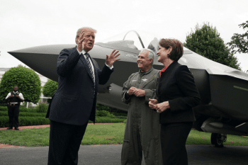 President Donald Trump talks to Chairman, President and CEO of Lockheed Martin Marilyn Hewson and Director and Chief Test Pilot Alan Norman in front of an F-35 fighter jet in 2018. [Source: politico.com]