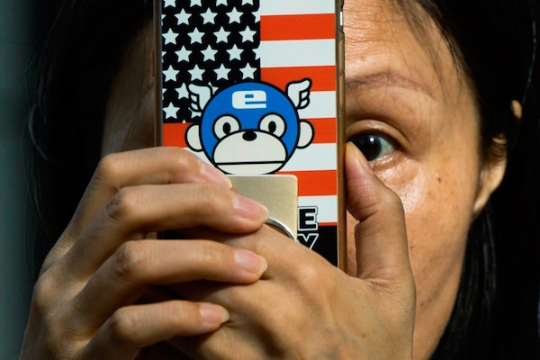 A woman takes a photo with a phone that has a United States flag themed cover outside the United States Consulate in Chengdu in southwest China's Sichuan province on, July 26, 2020. Ng Han Guan | AP