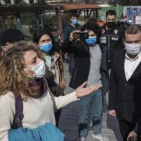 A supporter of Bogazici University students talks to police officers outside a courthouse in Istanbul, Thursday, Feb. 11 2021