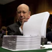 Goldman Sachs Chairman and CEO Lloyd Blankfein examines a report on his company by the Senate Permanent Subcommittee on Investigations before a 2010 hearing on Wall Street investment banks and the financial crisis. (AP)