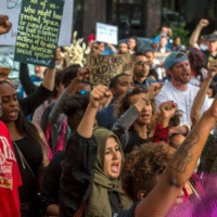 """UC Davis student Kaleemah Muttaqi, 19, center with green scarf, joined the """"Fists Up"""" chant during a Day of Action protest in downtown Sacramento hosted by Black Lives Matter Sacramento and the Anti Police-Terror Project in Sacramento, Calif., on Wed., April 4, 2018. They are seeking justice for Stephon Clark who was killed by Sacramento police in his grandmother's backyard. RENEE C. BYER RBYER@SACBEE.COM Read more here: https://www.sacbee.com/opinion/op-ed/article248636275.html#storylink=cpy"""