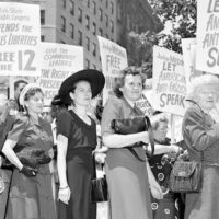 A mass demonstration is held in front of Federal Courthouse in New York City, June 6, 1949, to protest against the 'Communist conspiracy' show trial. The defendants, leaders of the Communist Party USA, were charged under the Smith Act. Joining the picket line at Foley Square are the wives of three of the twelve defendants, starting third from left, Lillian Gates, wife of Daily Worker editor John Gates; Fern Winston, wife of CPUSA leader Henry Winston; and Elizabeth Hall, wife of Ohio CP leader Gus Hall. | AP