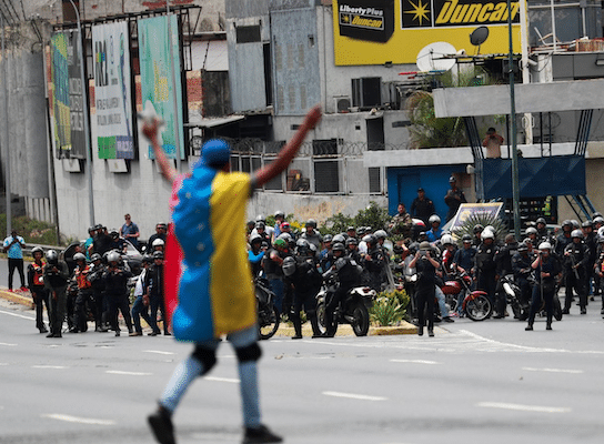 A demonstrator covered with a Venezuelan flag gestures in front of security forces during a protest in Caracas, Venezuela, on March 10, 2020. Carlos Jasso/Reuters