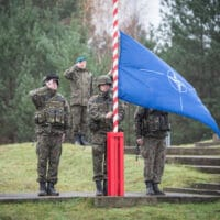 Raising of the NATO flag DRAWSKO POMORSKIE TRAINING AREA, Poland--The NATO flag is raised during the opening ceremony for Exercise Steadfast Jazz here Nov. 3. Exercise Steadfast Jazz 2013 is taking place from 1-9 November in a number of Alliance nations including the Baltic States and Poland. The purpose of the exercise is to train and test the NATO Response Force, a highly ready and technologically advanced multinational force made up of land, air, maritime and special forces components that the Alliance can deploy quickly wherever needed. The Steadfast series of exercises are part of NATO's efforts to maintain connected and interoperable forces at a high-level of readiness. (NATO photo by British army Sgt. Ian Houlding)