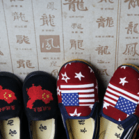 Chinese made children's shoes embroidered with Chinese maps and U.S. flags are on display at a shop in Beijing. Andy Wong | AP