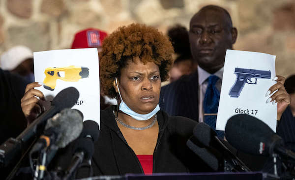Naisha Wright, Daunte Wright's aunt, shows pictures of a Glock 17 and a Taser X26P during a press conference at New Salem Missionary Church in Minneapolis, Minnesota, on April 15, 2021.