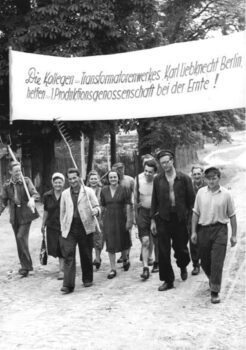 This photograph shows the arrival of workers from the city carrying a banner that reads 'Colleagues from the Karl Liebknecht Berlin transformer factory are helping the first production cooperative with the harvest!' The 1945/46, democratic land reform in the Soviet Occupation Zone secured food supplies in the dire post-war period while also fundamentally changing the system of land ownership in East Germany. Roughly 560,000 small farms emerged from the redistribution scheme, but they were often poorly equipped and supplied. Urban industrial and craft enterprises stepped in to help with the harvest in the emerging agricultural cooperatives.