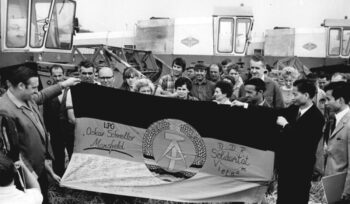 This image from 1972 shows cooperative farmers handing over a flag of solidarity to the ambassador of the Democratic Republic of Vietnam. 'Solidarity hastens victory' was the motto under which the citizens of the DDR expressed their solidarity with the Vietnamese people and against the United States' criminal war. Enthusiasm to donate for the cause of the Vietnamese was extraordinary: by 1975, more than 442 million East German Mark had been collected. The victory of the North Vietnamese troops on 1 May 1975 was celebrated in the streets of Berlin, singing 'Everybody on the street, May is red, everybody on the street, Saigon is free'.