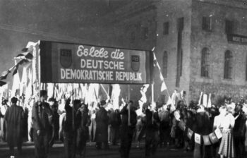 This photograph shows a mass rally with the Free German Youth that marked the founding of the German Democratic Republic in the Soviet occupation zone. Six months before that, in May 1949, the Federal Republic of Germany had been founded on the territory of the three western occupation zones. The DDR broke with Germany's imperialist past, defined itself as a workers' and farmers' state, built socialism, and integrated itself economically and militarily into the Eastern Bloc alliances.