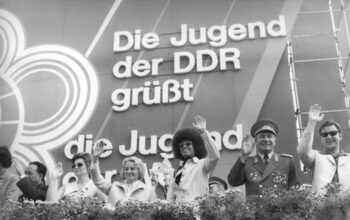 In 1973, the Free German Youth (FDJ), a member of the World Federation of Democratic Youth, hosted the Tenth World Festival of Youth and Students in Berlin. 25,600 guests from 140 countries met with eight million young DDR citizens to celebrate, discuss, and advocate for world peace and international cooperation. Among the guests was Black Power activist Angela Davis (here in the grandstand next to People's Education Minister Margot Honecker and Soviet cosmonaut Valentina Tereshkova).