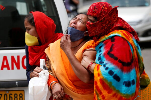 A woman is consoled after her husband died due to the coronavirus disease (COVID-19) outside the mortuary of a COVID-19 hospital in Ahmedabad, India, April 20, 2021
