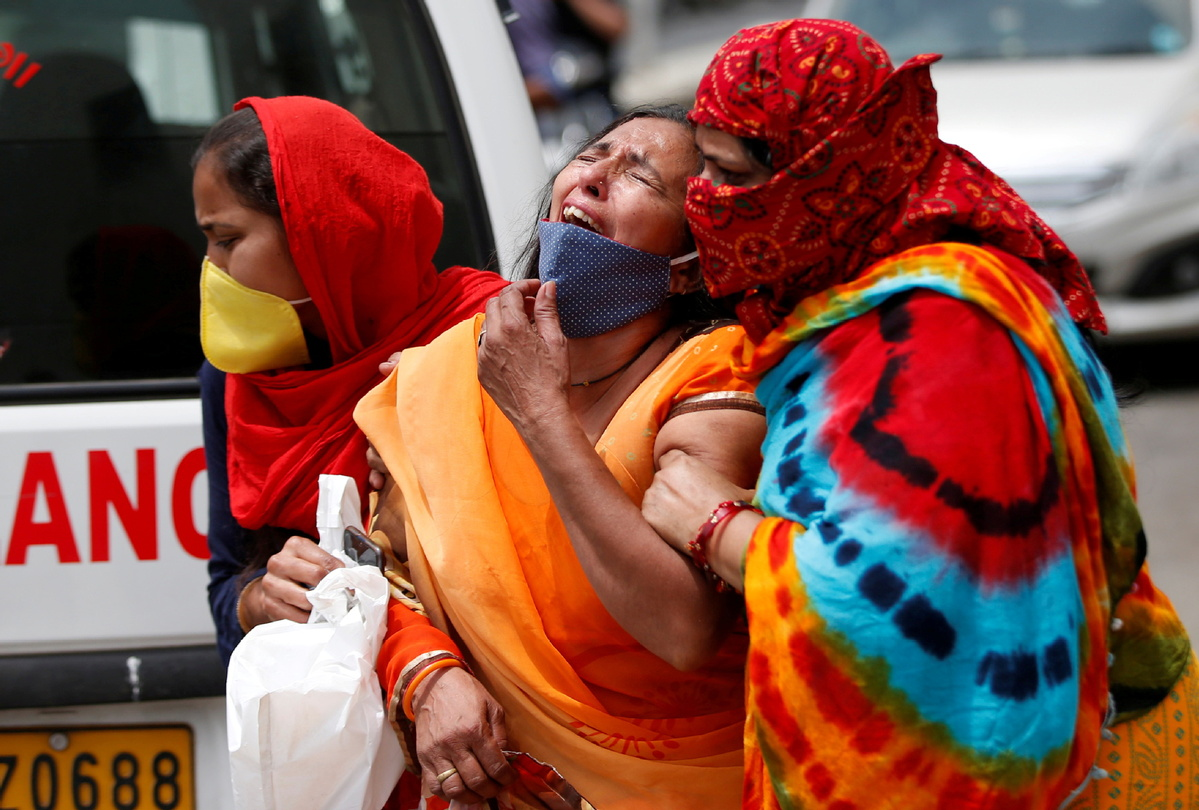 | A woman is consoled after her husband died due to the coronavirus disease COVID19 outside the mortuary of a COVID19 hospital in Ahmedabad India April 20 2021 | MR Online