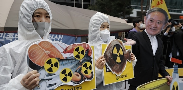 Environmental activists wearing a mask of Japanese Prime Minister Yoshihide Suga and protective suits perform to denounce the Japanese government's decision on Fukushima water, near the Japanese embassy in Seoul, South Korea