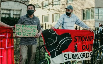 Tenants and supporters hold signs facing the street. One on the left reads, 'because of the pandemic, no food, no rent.' Eleanor Goldfield | ArtKillingApathy.com