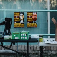 Two posters with messages for DC Council members Pinto and McDuffie behind supply tables at the rally. Eleanor Goldfield | ArtKillingApathy.com