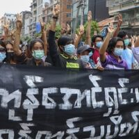 "Anti-coup protesters flash the three-finger salute, holding banner read "" Yangon Strike will defeat all enemies"" during a demonstration against the military coup in Yangon, Myanmar, on Monday, April 26, 2021"