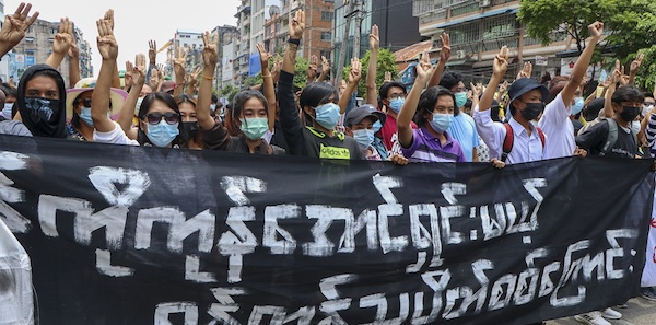 """Anti-coup protesters flash the three-finger salute, holding banner read """" Yangon Strike will defeat all enemies"""" during a demonstration against the military coup in Yangon, Myanmar, on Monday, April 26, 2021"""