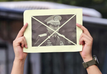 An activist holds up a defaced portrait of Myanmar's Commander-in-Chief, Senior General Min Aung Hlaing, during a rally against the military coup in Jakarta, Indonesia, Saturday, April 24, 2021. Southeast Asian leaders met Myanmar's top general and coup leader in an emergency summit in Indonesia Saturday. | Tatan Syuflana / AP