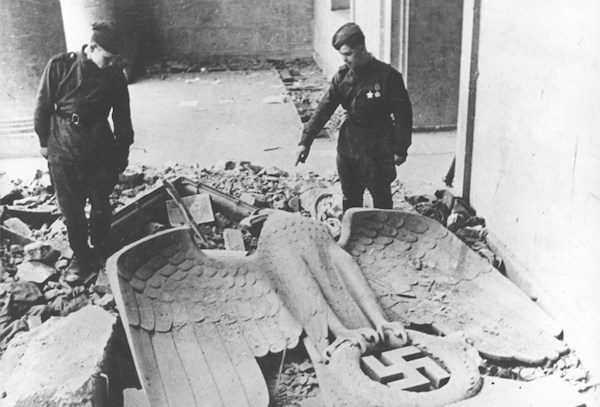 By April 1945, troops of the anti-Hitler coalition had liberated most of the territories occupied by the fascist Wehrmacht. The Red Army opened its offensive on the capital of the German Reich and the fierce 'Battle of Berlin' ended with the complete military defeat of Nazi Germany. This photograph shows two Red Army soldiers in the Reich Chancellery, Hitler's last command post. At their feet lies the toppled symbol of fascist power, the imperial eagle above the swastika.