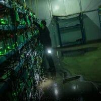 A worker checks the equipment inside a bitcoin mine in rural Sichuan province, 2016. Liu Xingzhe/People Visual