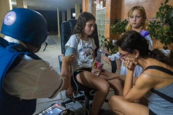 An paramedic checks the blood pressure of a young Israeli girl after her building was hit by a rocket in Ashkelon, May 12, 2021. Tsafrir Abayov   AP