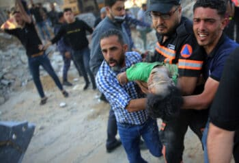 Palestinians carry the body of a child found in the rubble home destroyed by a precision Israeli airstrikes in Gaza, May 13, 2021. Abdel Kareem Hana   AP