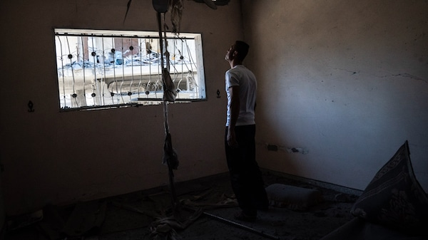 Mahmoud Ahmed, 34, gives a tour of his apartment, which was severely damaged by an Israeli airstrike on a neighboring building, May 24, 2021, in Magazzi, the Gaza Strip. John Minchillo | AP