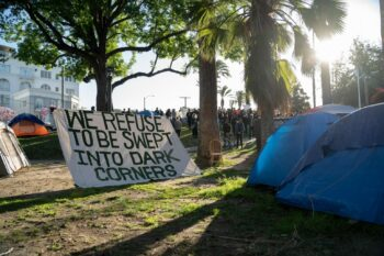 """A banner in Echo Park Lake that reads, """"We Refuse to be Swept into Dark Corners."""" Photo credit: Jeremy Lindenfeld / WhoWhatWhy"""