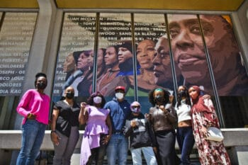 | From left Dr Ala Stanford Ajeenah Amir Sajda Purple Blackwell artist Russell Craig Pam Africa Krystal Strong YahNé Ndgo and Kezia Ridgeway stand in front of the East side of the Crown mural that pays homage to their social justice work at Philadelphias Municipal Services Building Photo Kimberly Paynter WHYY | MR Online