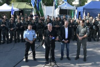 BENJAMIN NETANYAHU AND MINISTER OF PUBLIC SECURITY AMIR OHANA (CENTER RIGHT) SPEAK IN FRONT OF PHALANX OF ISRAELI FORCES IN LYDD (LOD), MAY 13, 2021 (PHOTO: TWITTER)