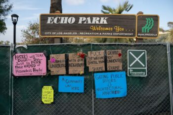 The fence surrounding Echo Park Lake is decorated with signs on April 24, 2021. Photo credit: Jeremy Lindenfeld / WhoWhatWhy