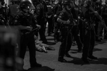 A protester is arrested and dragged on asphalt by police officers. Photo credit: Jeremy Lindenfeld / WhoWhatWhy