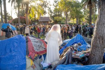 A homeless Echo Park Lake resident dons her wedding dress during a protest against her eviction. Photo credit: Jeremy Lindenfeld / WhoWhatWhy