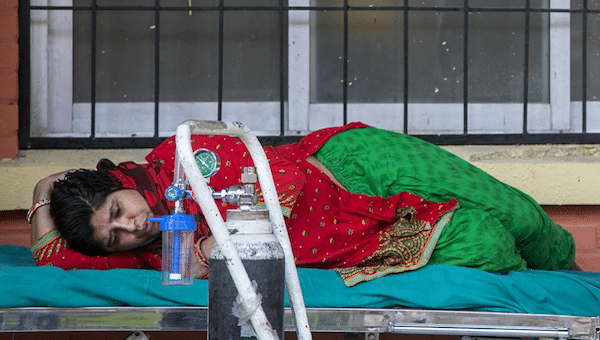 A COVID-19 patient waits to receive oxygen outside an emergency ward of a hospital in Kathmandu, Nepal