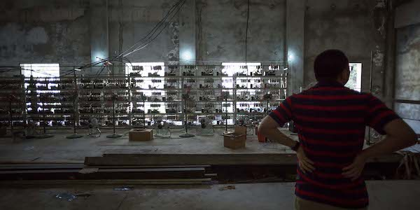 A man shows off equipment inside a Bitcoin mine near Kongyuxiang, Sichuan province, Aug. 12, 2016. Paul Ratje for The Washington Post via Getty Images/People Visual