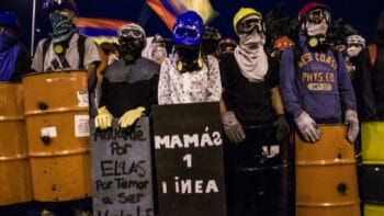 """A group of protesters from the first line stand behind their homemade shields during a Bogotá demonstration as Colombia's national strike continues. Among them, the """"First Line Mothers,"""" a group of mothers who stand together against police violence / credit Antonio Cascio"""