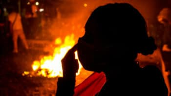 Silhouette of a woman in front of a fire on the streets of Bogotá during Colombia's national strike / credit: Antonio Cascio