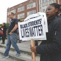 """Felecia Bazie, 18, a senior and president of Associated Student Government at Garfield High School, holds signs following a """"Black Lives Matter"""" rally Oct. 19, 2016 at the school in Seattle. Teachers, students and parents across Seattle public schools wore """"Black Lives Matter"""" shirts to promote racial equity in schools. (AP Photo/Ted S. Warren)"""