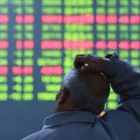 An investor looks on as prices fall at a stock brokerage house in Hangzhou, China. (Photo: Canadian Dimension - Shutterstock)