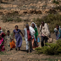 People walk from a rural area towards the town of Agula in the Tigray region of northern Ethiopia, where the Relief Society of Tigray was distributing food. (Ben Curtis/AP)