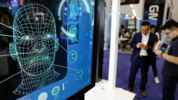 Visitors check their phones behind the screen advertising facial recognition software during the Global Mobile Internet Conference (GMIC) at the National Convention in Beijing, China, April 27, 2018. [Source: pri.org]