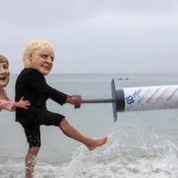 Vaccine equity campaigners posing as the leaders of G7 nations tussle over a giant mock syringe on June 11, 2021 near Falmouth, Cornwall, United Kingdom. (Photo: Andrew Aitchison/In Pictures via Getty Images)